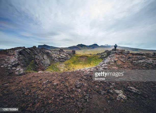 man standing on top of volcanic crater - terreno accidentato foto e immagini stock