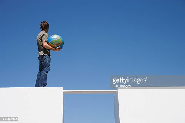 Man standing on wall outdoors with globe
