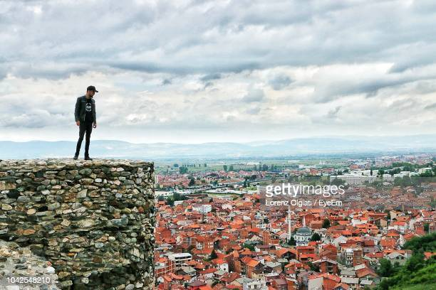 man standing on wall over townscape against sky - kosovo stock pictures, royalty-free photos & images