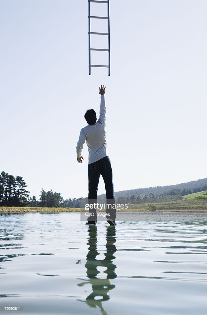 Man standing on water reaching for ladder rear view : Stock Photo