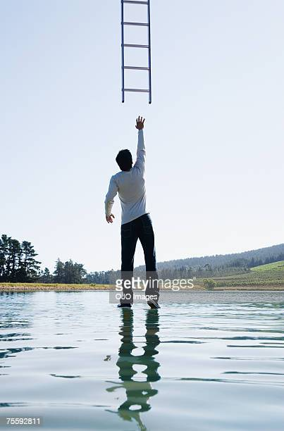 man standing on water reaching for ladder rear view - reaching stock pictures, royalty-free photos & images
