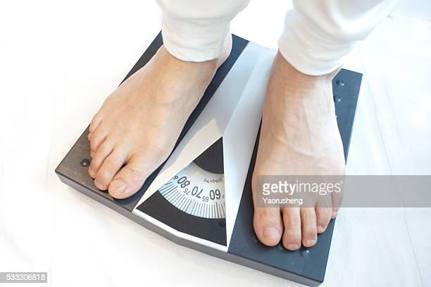 Man standing on weight scales with bare foot