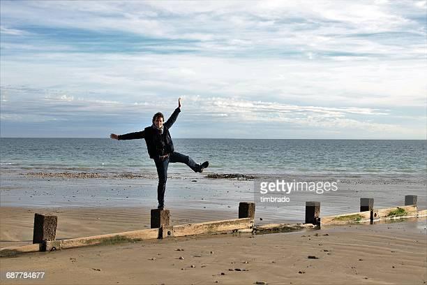 man standing on wooden post on beach, la rochelle, france - la rochelle fotografías e imágenes de stock