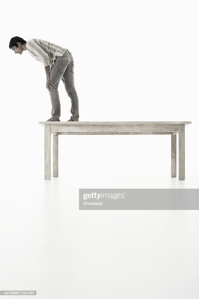 Man standing on wooden table looking down against white background, side view : Stockfoto