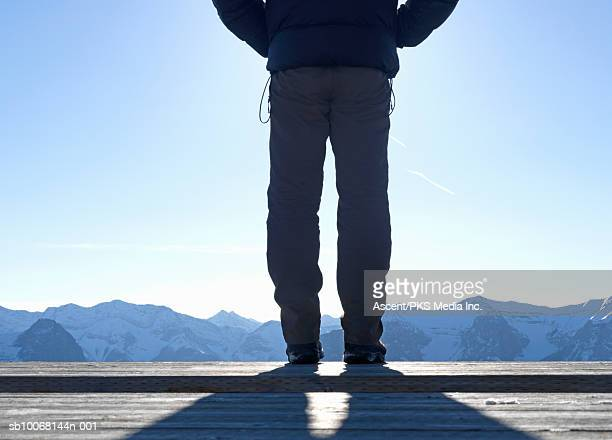 Man standing on wooden terrace, mountains in background, low section