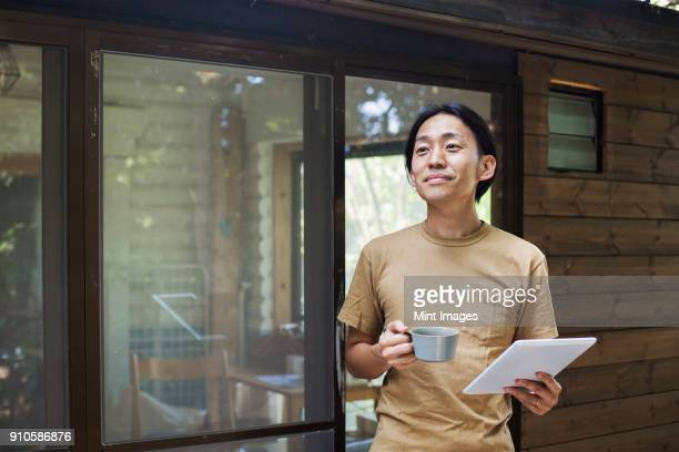 man standing outdoors, holding coffee mug and digital tablet. - 30代 ストックフォトと画像