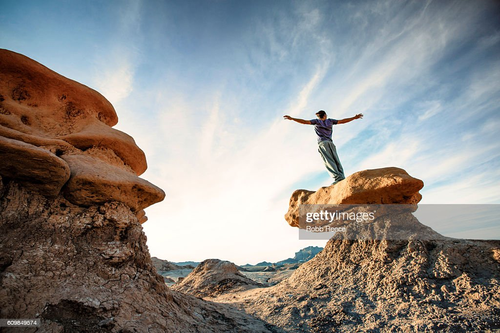 A man standing outdoors on a rock formation in the desert : Stock Photo