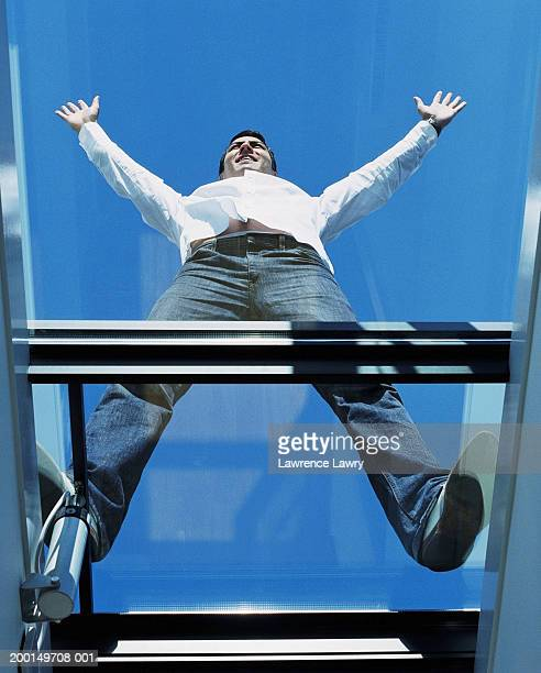 Man standing outdoors on skylight, view through glass from below