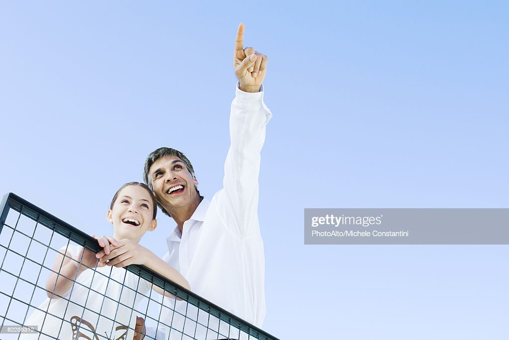 Man standing outdoors with daughter, pointing at the sky, both looking up and smiling, low angle view : Stock Photo