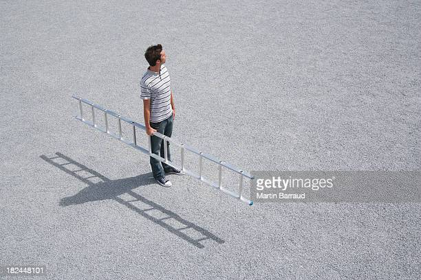 Man standing outdoors with ladder