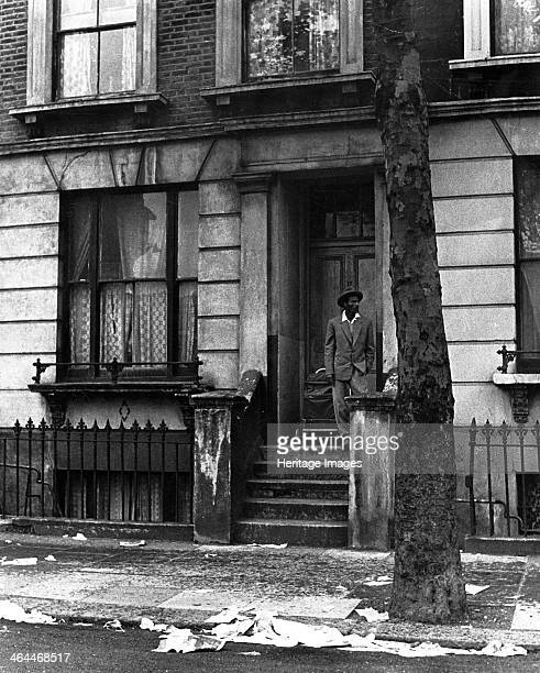 Man standing outside a house in Westbourne Grove, possibly in Kensington, London, 1950s.