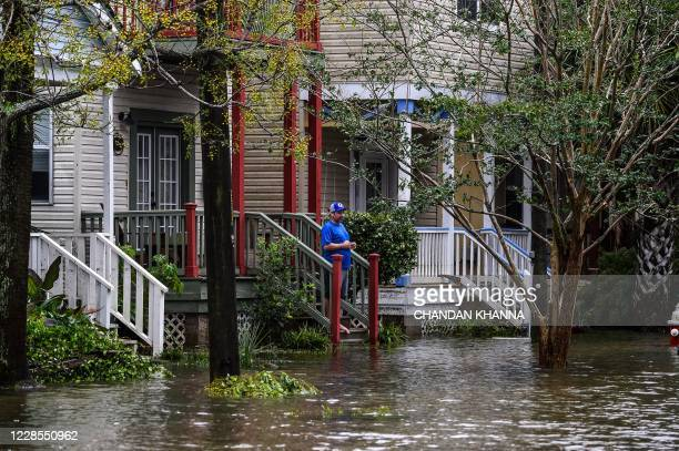 TOPSHOT A man standing outside of his homewatches a street flooded by Hurricane Sally in Pensacola Florida on September 16 2020 Hurricane Sally...