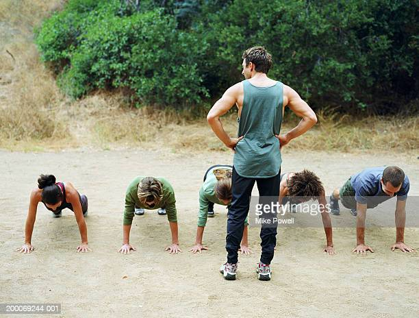 Man standing over group of people doing pushups, rear view