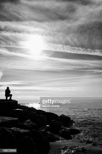 HOMME DEBOUT Pier regardant l'océan, noir et blanc