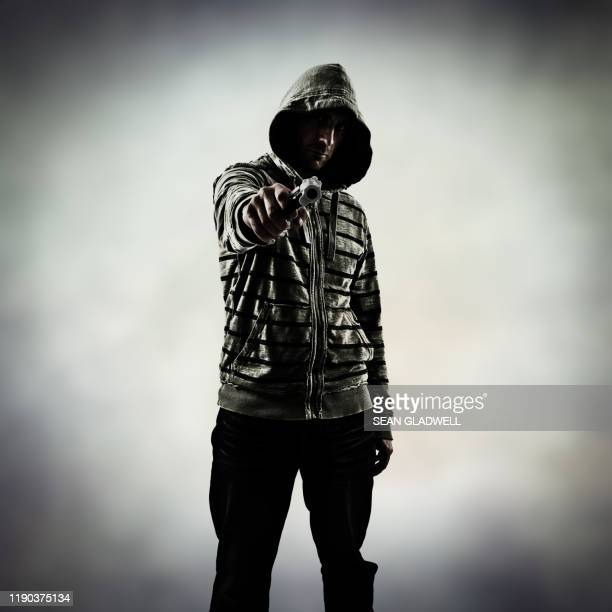 man standing pointing handgun - murderer stock pictures, royalty-free photos & images