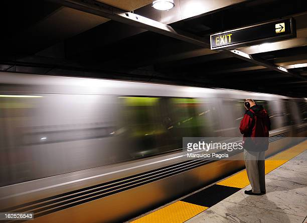 Man standing still very close to the train rails, listening to his music. The man is wearing a red and black jacket and a light gray trousers. An...