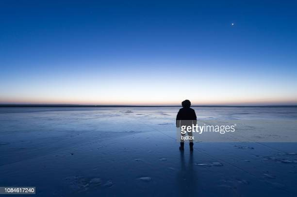 man standing the frozen lake at dawn - man blue background stock pictures, royalty-free photos & images