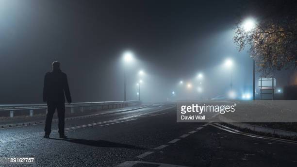 a man standing to his back to the camera, wearing a winter coat. looking down an empty road on a moody, atmospheric, spooky night. on a foggy winters evening. - low stock pictures, royalty-free photos & images