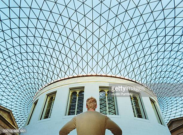 Man standing under glass roof, arms akimbo, low angle view