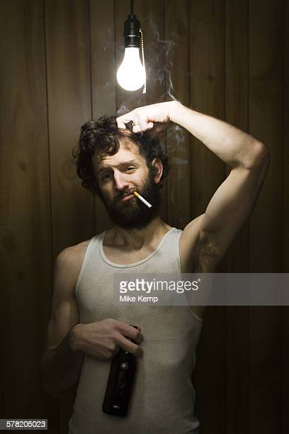 man standing under light bulb with cigarette and beer bottle - incandescent bulb fotografías e imágenes de stock