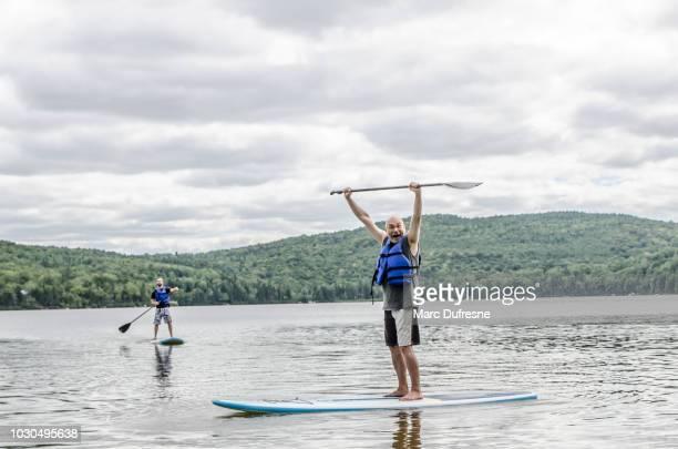 mann oben auf paddleboard auf einem see sommer tagsüber - first occurrence stock-fotos und bilder