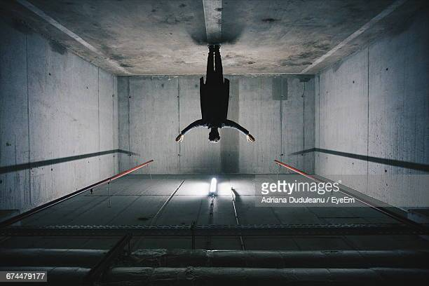 man standing upside down in concrete room - upside down stock pictures, royalty-free photos & images