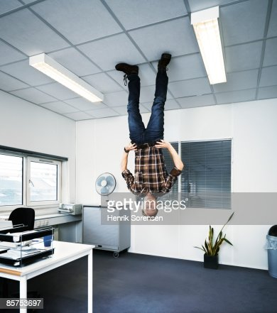 Man Standing Upside Down On The Ceiling Stock Photo