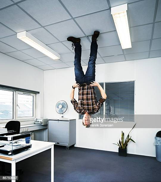 man standing upside down on the ceiling. - op z'n kop stockfoto's en -beelden