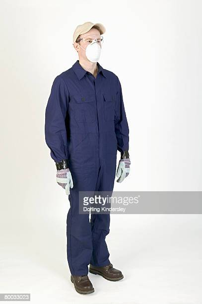 Man standing, wearing overalls, mask, gloves and cap