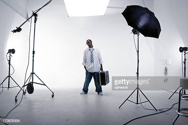 A man standing with a case in a white studio with lighting