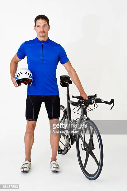 A man standing with a racing bike