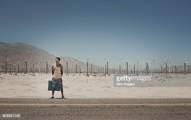 a man standing with a suitcase on the side of a highway, with wind turbines in the background.  - 25 29 años fotografías e imágenes de stock