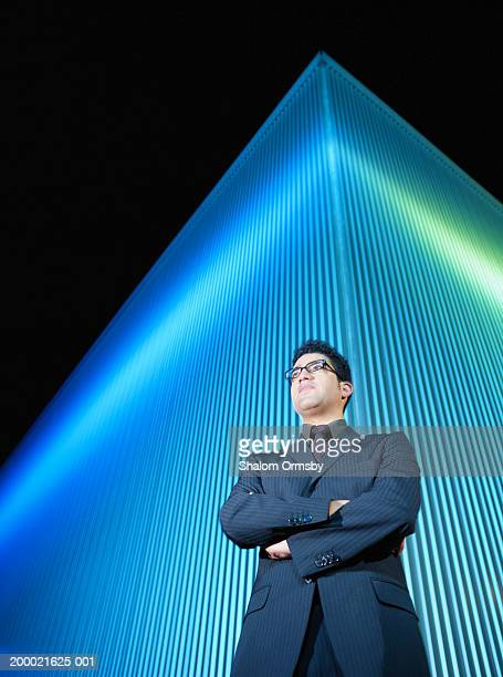 Man standing with arms crossed in front of office building at night