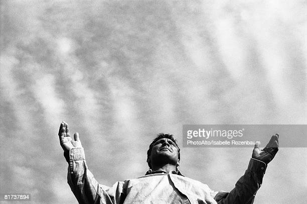 Man standing with arms out, low angle view
