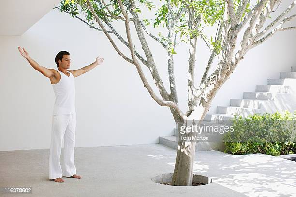 Man standing with arms outstretched in courtyard