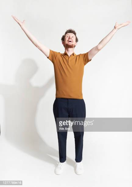 man standing with arms outstretched - males stock pictures, royalty-free photos & images
