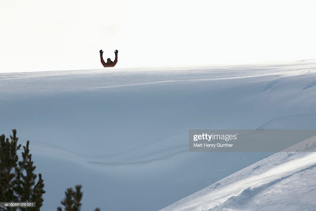 Man standing with arms up behind snow : Stockfoto