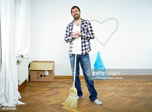 Man standing with broom against heart shape on wall, Munich, Bavaria, Germany