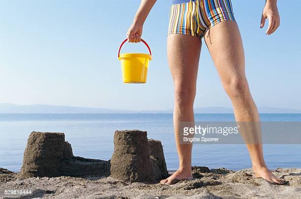 Man Standing with Bucket Beside Sandcastle on Beach