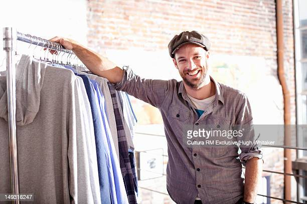 Man standing with clothes on rack