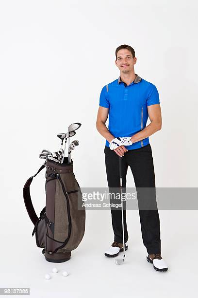 A man standing with golfing equipment