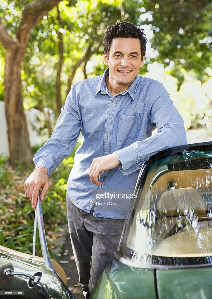 Man standing with green convertible classic car : Stock Photo