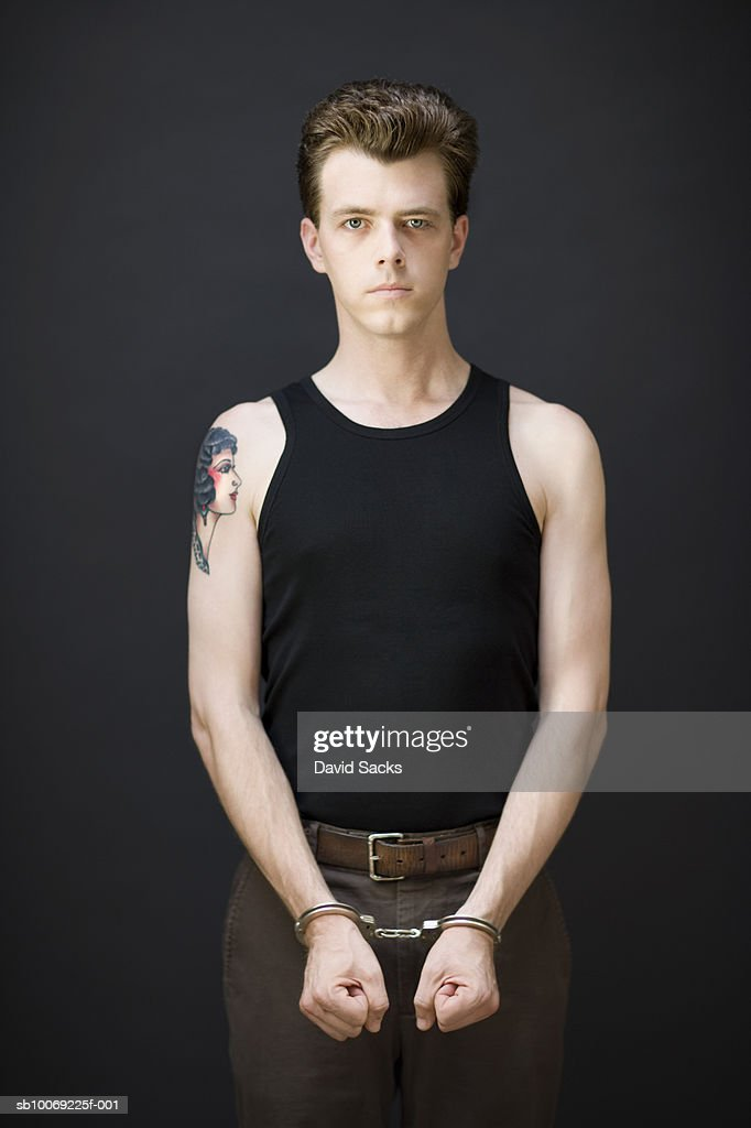 Man standing with handcuffs, portrait : Stockfoto