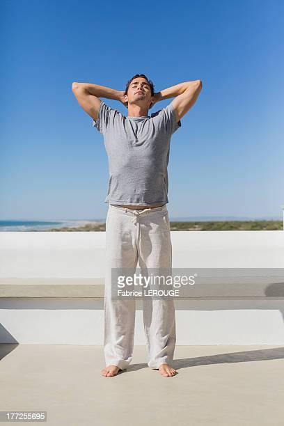 man standing with hands behind head - white pants fotografías e imágenes de stock