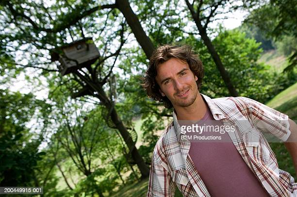 Man standing with hands on hips, portrait, tree house in background