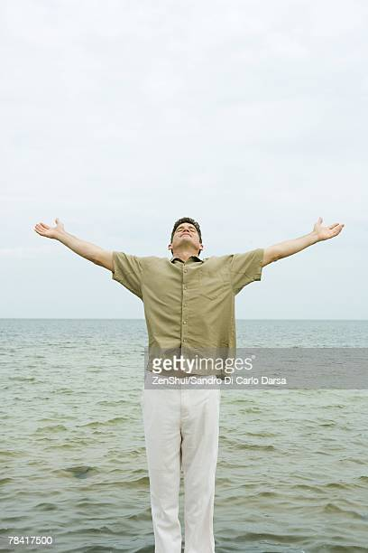 man standing with head back and arms out, in front of ocean - maniche corte foto e immagini stock