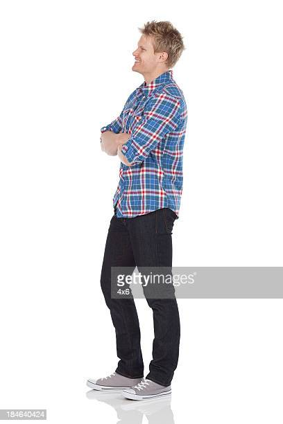 man standing with his arms crossed - van de zijkant stockfoto's en -beelden