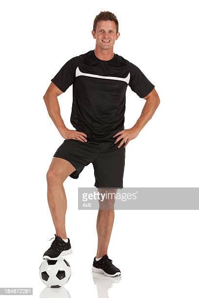 Mann stehend mit seinem einem Fuß auf einem Fußball-ball