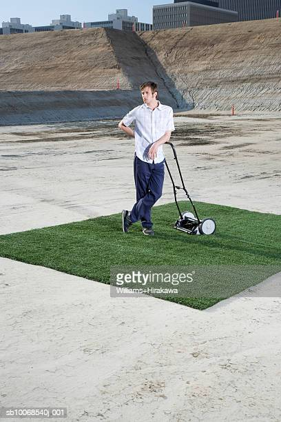 Man standing with lawn mower on patch of grass at construction site
