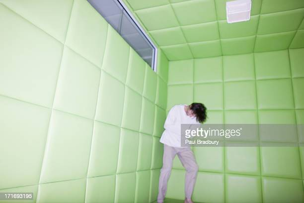 Man standing with leaning in padded room